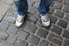 Jugendbeine in den Turnschuhen und in Blue Jeans, die auf Pflastersteinen stehen Lizenzfreie Stockbilder
