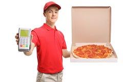 Jugendbote, der eine Pizza und einen Zahlungsanschluß hält stockbilder