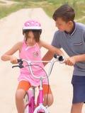 Jugendbruder, der seine jüngere Schwester unterrichtet, ein Fahrrad zu reiten Kleines Mädchen in einem rosa Schutzhelm auf Fahrte lizenzfreies stockbild