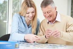 Jugendenkelin-helfender Großvater mit Puzzlen Stockbilder