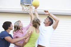 Jugendfamilie, die Basketball außerhalb der Garage spielt Stockbild