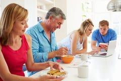 Jugendfamilie, die in der Küche mit Laptop frühstückt Stockbilder