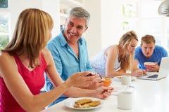 Jugendfamilie, die in der Küche mit Laptop frühstückt Lizenzfreies Stockbild