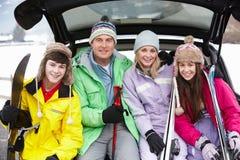 Jugendfamilie, die in der Matte des Autos mit Skis sitzt stockfoto