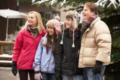 Jugendfamilie, die entlang Snowy-Stadtstraße geht Stockbilder