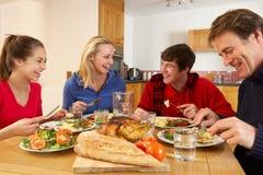 Jugendfamilie, die zusammen das Mittagessen in der Küche isst Lizenzfreie Stockfotografie