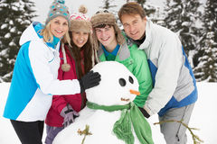 Jugendfamilien-Gebäude-Schneemann am Ski-Feiertag Lizenzfreies Stockfoto
