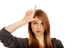 Jugendfrau macht Verliererzeichen auf ihrer Stirn lizenzfreie stockbilder