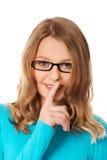 Jugendfrau mit dem Finger auf Lippen stockbilder