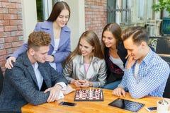 Jugendfreunde, die ein Schachspiel spielen und auf einem Caféhintergrund denken Schachspielkonzept stockfoto