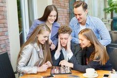 Jugendfreunde, die ein Schachspiel spielen und auf einem Caféhintergrund denken Schachspielkonzept lizenzfreie stockbilder