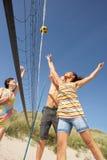 Jugendfreunde, die Volleyball auf Strand spielen Lizenzfreie Stockfotos