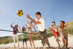 Jugendfreunde, die Volleyball auf Strand spielen lizenzfreie stockfotografie