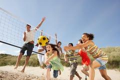 Jugendfreunde, die Volleyball auf Strand spielen Stockbilder