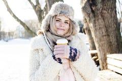 Jugendhippie-Mädchen der Junge recht im Freien im Winterschneepark, der den trinkenden Kaffee des Spaßes, das glückliche Lächeln  Lizenzfreie Stockfotos