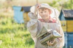 Jugendimker, der einen Raucher auf Bienenyard verwendet Lizenzfreie Stockfotos