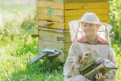 Jugendimker mit gemalten hölzernen Bienenstöcken Stockfotografie