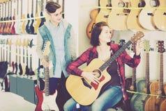 Jugendkunden, die Ampere und Akustikgitarre in der Gitarre SH vergleichen Stockbilder