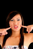 Jugendlich asiatische amerikanische Frauenfinger zu den Backen Lizenzfreie Stockbilder
