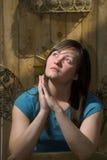 Jugendlich betet durch Gartenzaun Stockbild