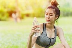 Jugendlich Blick des asiatischen Sports auf Trinkwasserflasche während Tätigkeit im Freien stockbild