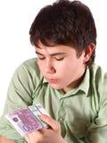 Jugendlich Blicke auf den Stapel des Geldes. stockfoto