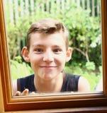 Jugendlich blonder Jungenblick durch das Fenster Lizenzfreie Stockfotos