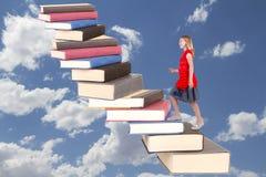 Jugendlich, ein Treppenhaus von Büchern kletternd Stockfotos