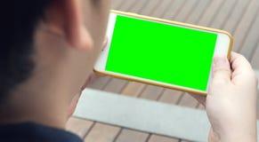 Jugendlich, einen Smartphone in den Händen eines grünen Schirmes halten stockbilder