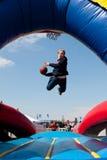 Jugendlich erhält den zerstreuten Versuch, Basketball im Karnevals-Spiel einzutauchen Lizenzfreies Stockfoto
