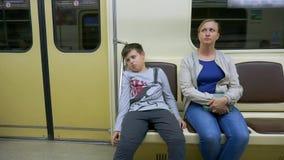 Jugendlich Fahrten des Sohns die U-Bahn mit ihrer Mutter Er ist nicht glücklich stock video footage