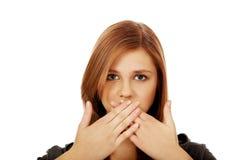 Jugendlich Frau, die ihren Mund mit beiden Händen bedeckt lizenzfreies stockfoto