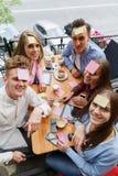 Jugendlich Freunde, die den Spaß spielt mit Aufklebern auf Stirnen auf einem Caféhintergrund haben Freundtätigkeitskonzept stockbild