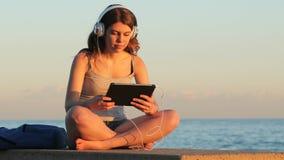 Jugendlich grasende und hörende Medien auf einer Tablette bei Sonnenuntergang