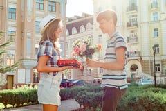 Jugendlich Junge beglückwünscht Mädchen mit Blumenstrauß von Blumen und von Geschenk, der im Freien glückliche Jugend Porträtpaar lizenzfreie stockbilder