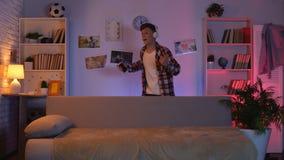 Jugendlich Junge in den Kopfhörern hörend auf die Musik und Tanzen, täuschend vor, berühmt zu sein stock video footage