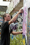 Jugendlich Junge, der auf Anstrich-Graffiti sich konzentriert lizenzfreie stockfotografie