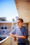 Jugendlich Junge, der auf Balkon-Schiene auf Sunny Day sich lehnt Stockfotos