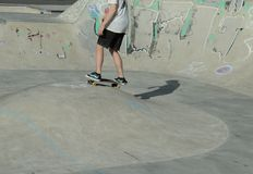 Jugendlich Junge, der in einen Sportpark Skateboard fährt Lizenzfreie Stockfotos