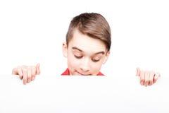 Jugendlich Junge, der leere Fahne lokalisiert auf Weiß hält Stockfotografie