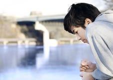 Jugendlich Junge, der traurig heraus über dem Fluss, denkend schaut Stockbilder
