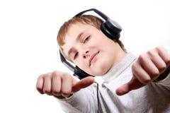 Jugendlich Junge, der zu den Kopfhörern hört Lizenzfreie Stockfotos