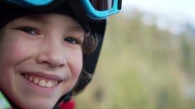 Jugendlich Junge in einem Sturzhelm und in den Schutzbrillen sitzt in einer Skiaufzugkabine Das Kind lacht glücklich Spaßfeiertag stock footage