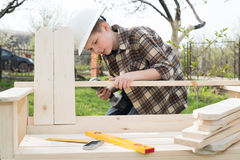 Jugendlich Junge im Sturzhelm mit einem Schraubenzieher, der einen Garten outd auf die Bank setzen lässt stockfotos