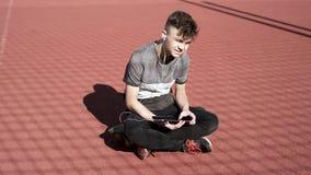 Jugendlich Junge mit Kopfhörern und Tablette stock footage