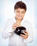 Jugendlich Junge mit Sparschwein lizenzfreie stockfotos