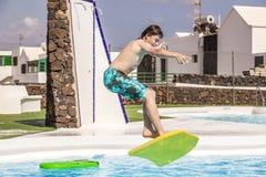 Jugendlich Junge springt in das Pool mit seinem Boogiebrett Lizenzfreies Stockbild