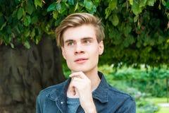 Jugendlich Junge unter dem romantischen Lächeln des Baums Lizenzfreie Stockbilder