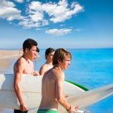 Jugendlich Jungen des Surfers, die auf Strandufer sprechen stockfoto
