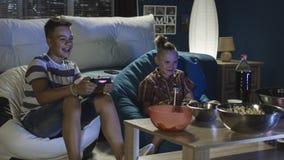 Jugendlich Jungen, die zusammen Videospiel auf Sofa spielen lizenzfreie stockfotos